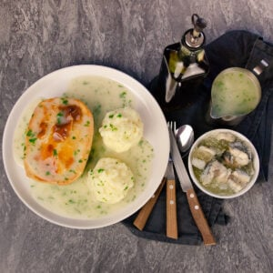 Pie Mash and Liquor served on a white plate with a knife, fork, spoon, a bowl of jellied eels, a jug of liquor and a bottle of chilli vinegar on the side