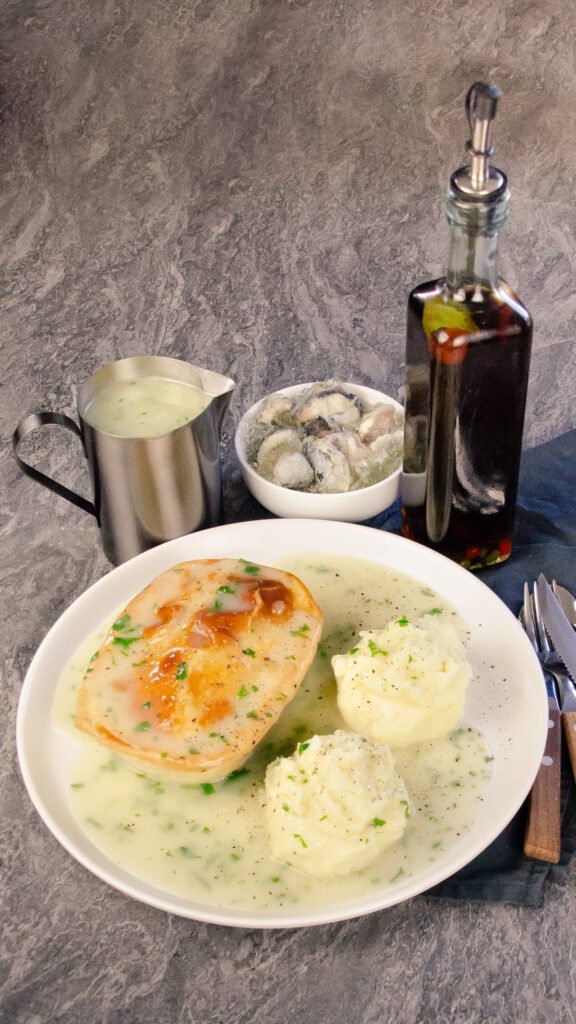 Traditional Pie Mash and Liquor served on a white plate with a knife,fork, spoon, a bowl of jellied eels, a jug of liquor and a bottle of chilli vinegar on the side