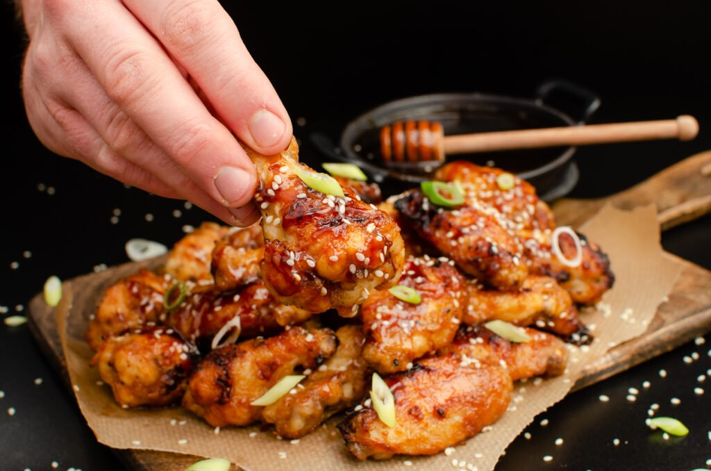 Holding a chicken drumette coated in honey garlic marinade with sesame seeds and spring onion by hand