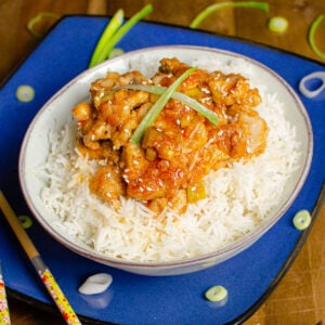 Diced Pork fillet with a spicy sauce served on rice with spring onions and sesames seeds scattered on top.