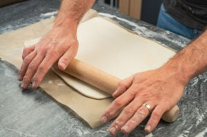 Rolling out puff pastry by hands with a wooden rolling pin