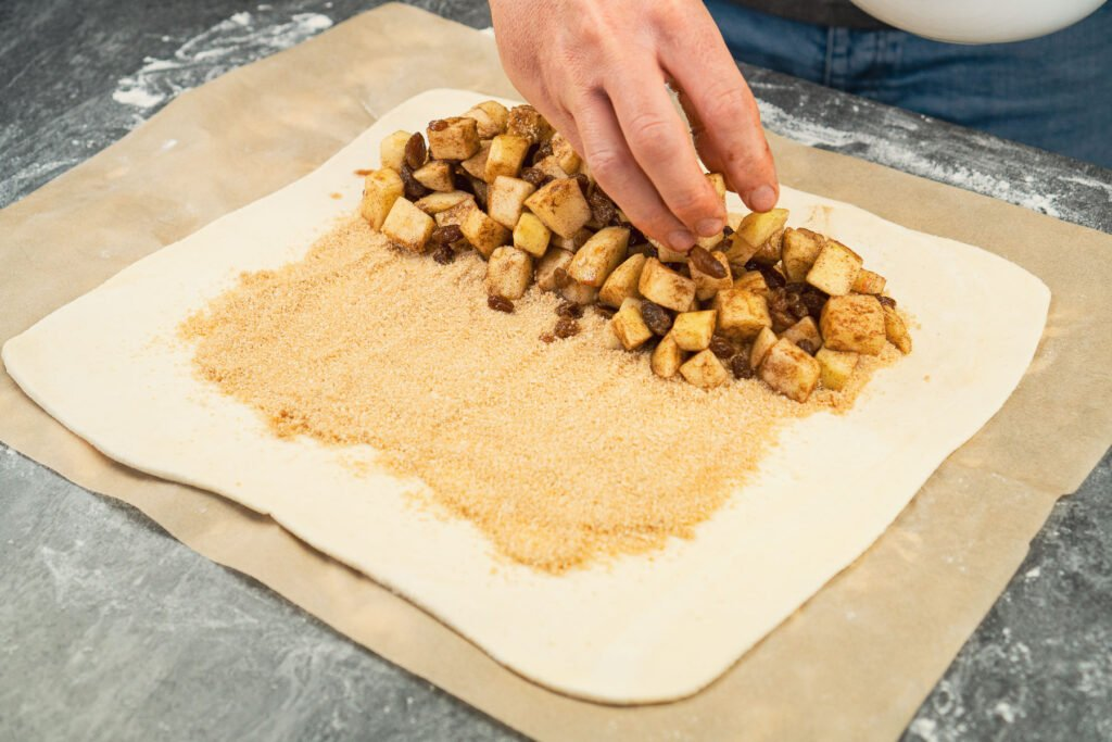 Placing chopped apple with sultans coated in cinnamon onto the breadcrumb mix on the puff pastry sheet