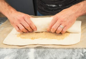 Rolling the puff pastry over the apple filling by hands to form a large parcel
