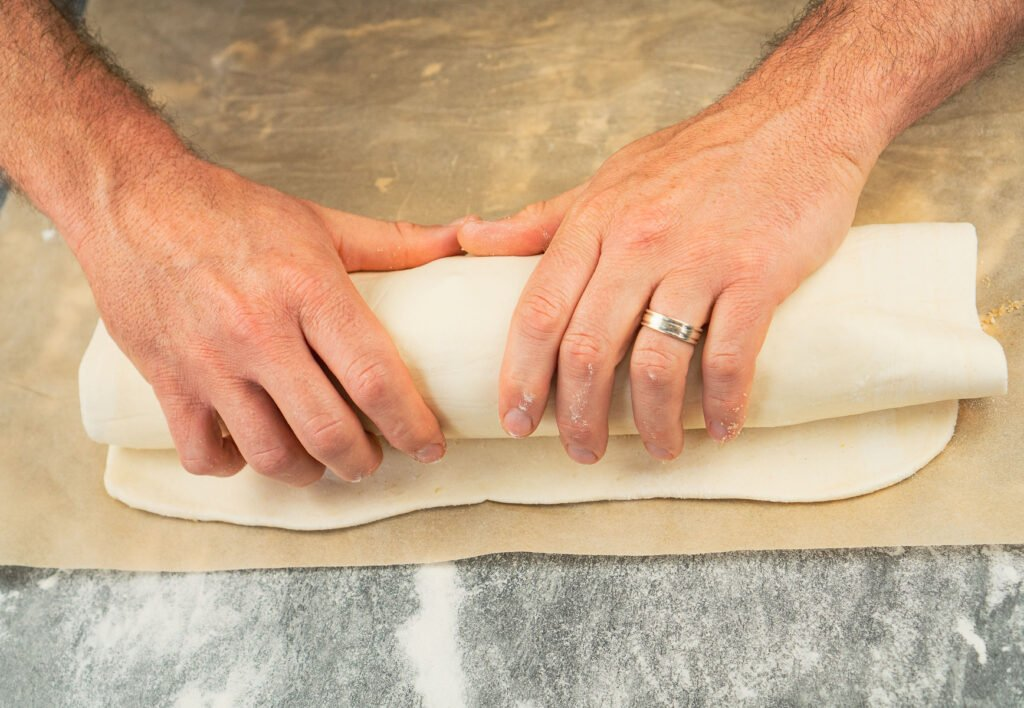 Rolling the puff pastry over the apple filling by hands to form the apple strudel