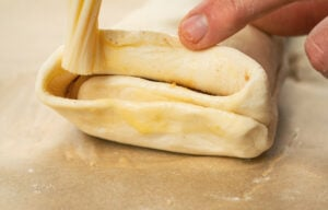Brushing the ends of the puff pastry parcel with egg wash