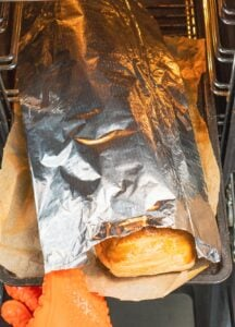 Apple strudel on a baking tray with a foil sheet over the top being placed into the oven by hand with a orange oven glove