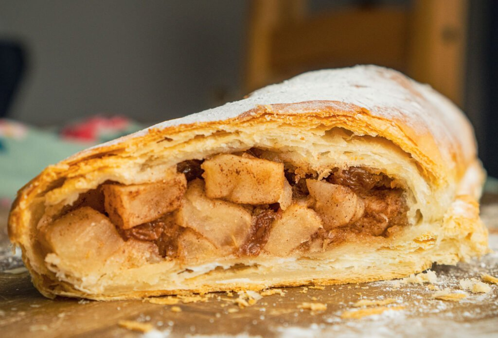 Apple strudel puff pastry dessert cut open with chunks of cinnamon apple and sultanas showing in the middle for the filling