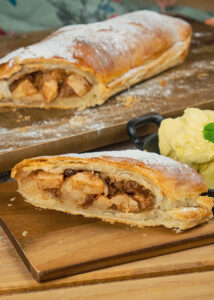 Apple strudel served on a wooden board with vanilla ice cream and the apple strudel in the background