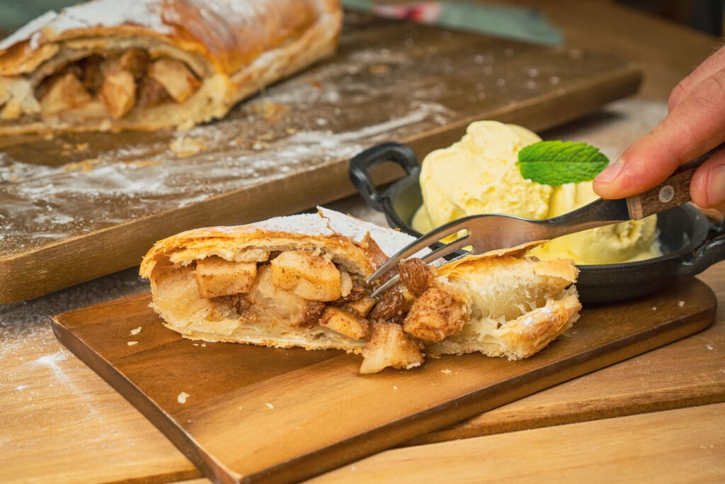 Chopping a piece of the apple strudel with a fork with ice cream in a black dish behind the dessert on a wooden board