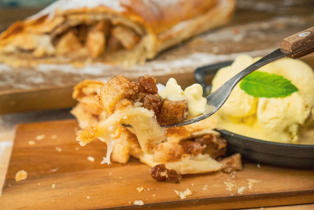 Apple strudel and ice cream on a fork ready to eat with the apple strudel and vanilla ice cream in the background