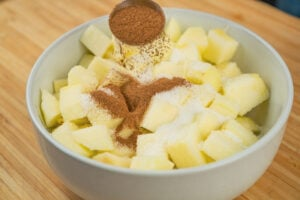 Chopped up apple in a white bowl coated with white sugar and cinnamon being sprinkled over the top