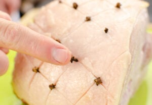 Pushing cloves into the fat of the gammon joint with fingers