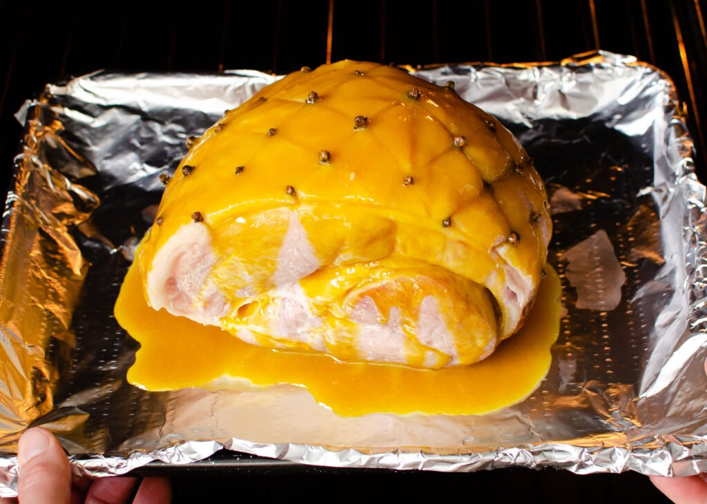 Glazed ham joint on a baking tray lined with tin foil being placed into the oven by hands