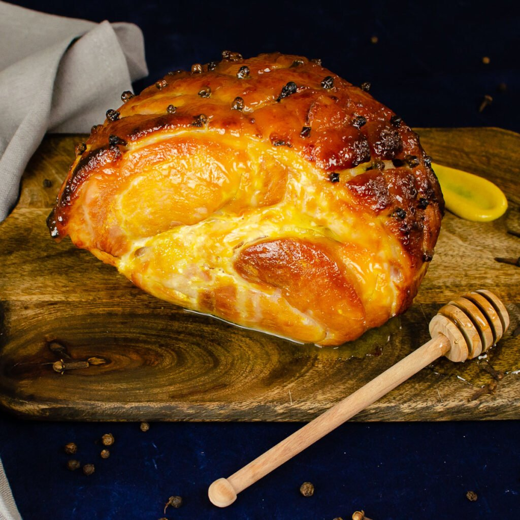 Honey Roast Gammon on a wooden board with a coated honey stick and a dollop of English mustard on the side