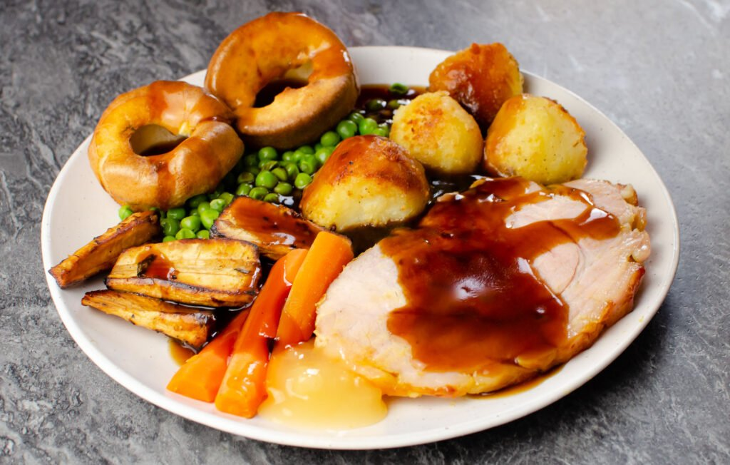 A sunday roast dinner served a white plate which consist of two slices of honey roast gammon, roast potatoes, peas, carrots , roasted parsnips, flawless Yorkshire puddings and apple sauce