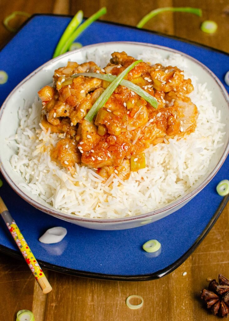 Hot and Spicy Pork served with rice in a green bowl on a blue plate with chopped spring onions on the sides