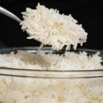 White basmati rice on a fork and a glass bowl of rice is underneath the fork