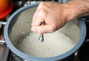 Placing a clear glass lid onto the silver pot by hand
