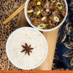 Pin image of our Pressure cooker Korean Beef Stew served in a white and blue bowl with spring onions and sesame seeds with a bowl of white rice next to it and chopsticks on the side