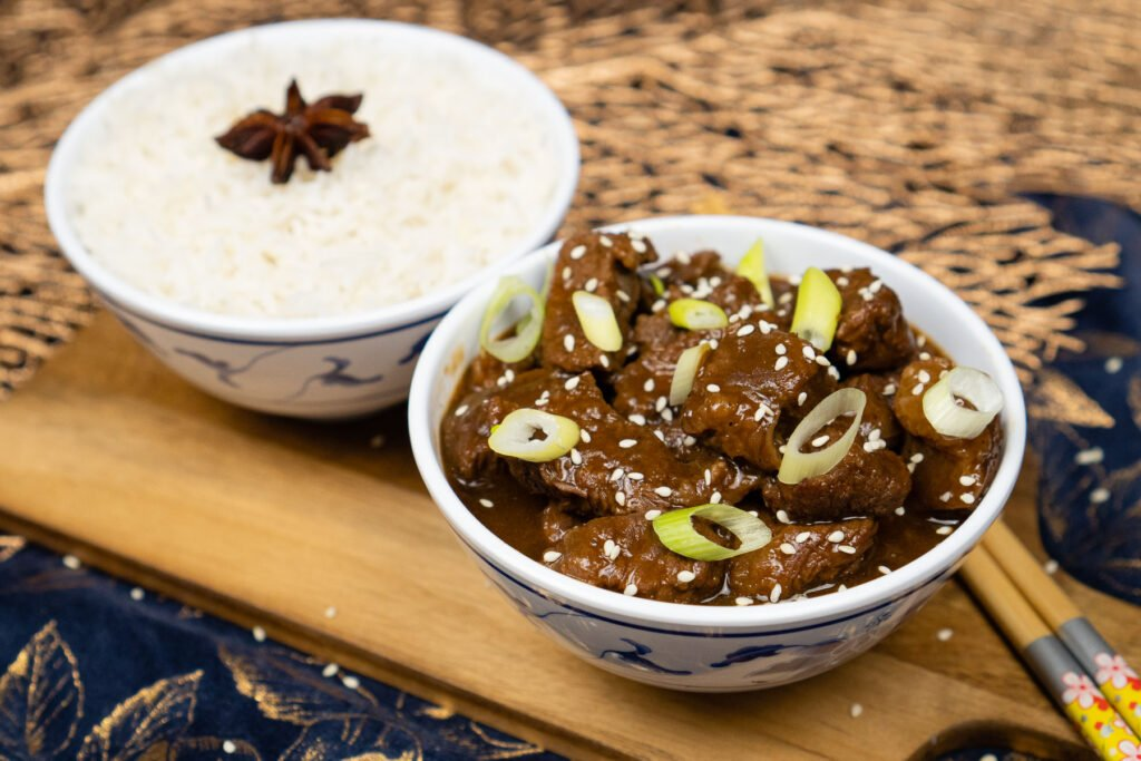 Pressure cooker Korean Beef Stew served in a white and blue bowl with spring onions and sesame seed on top and a bowl of white rice in the background and chopsticks on the side