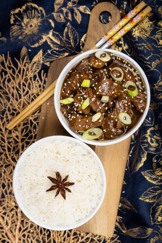 Pressure cooker Korean Beef Stew served in a white and blue bowl with spring onions and sesame seeds with a bowl of white rice next to it and chopsticks on the side