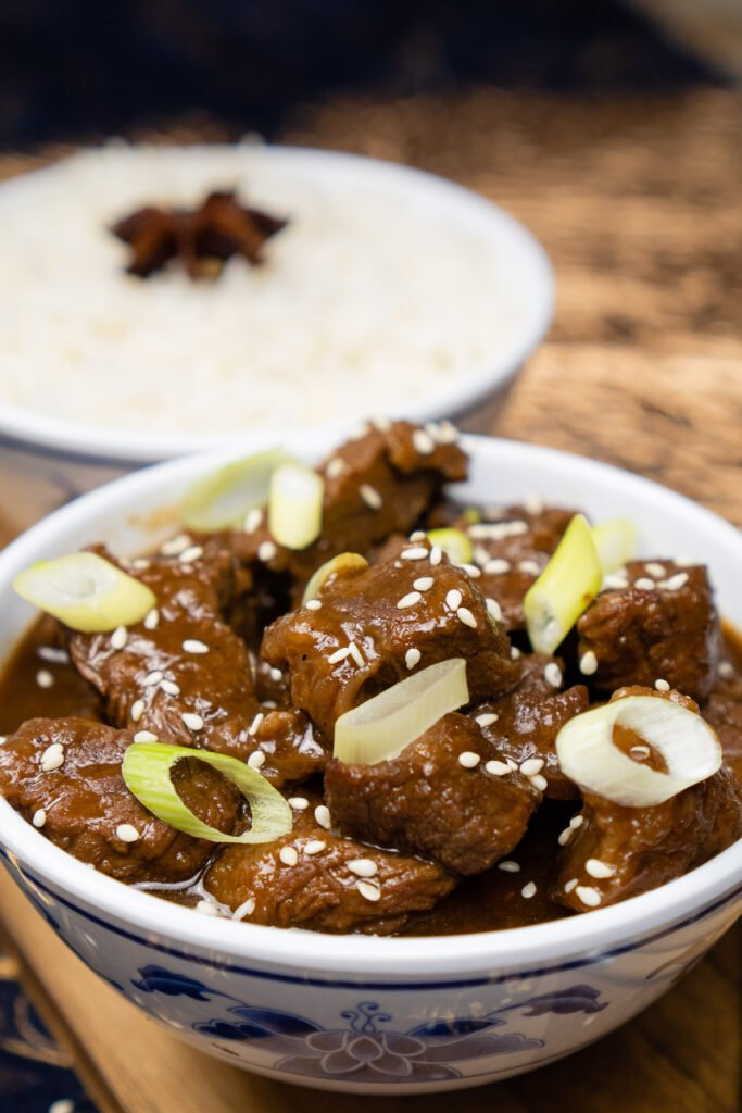 Pressure cooker Korean Beef Stew served in a white and blue bowl with spring onions and sesame seed on top and a bowl of white rice in the background