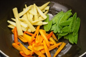 Mangetout,baby corn and chopped orange pepper in a wok