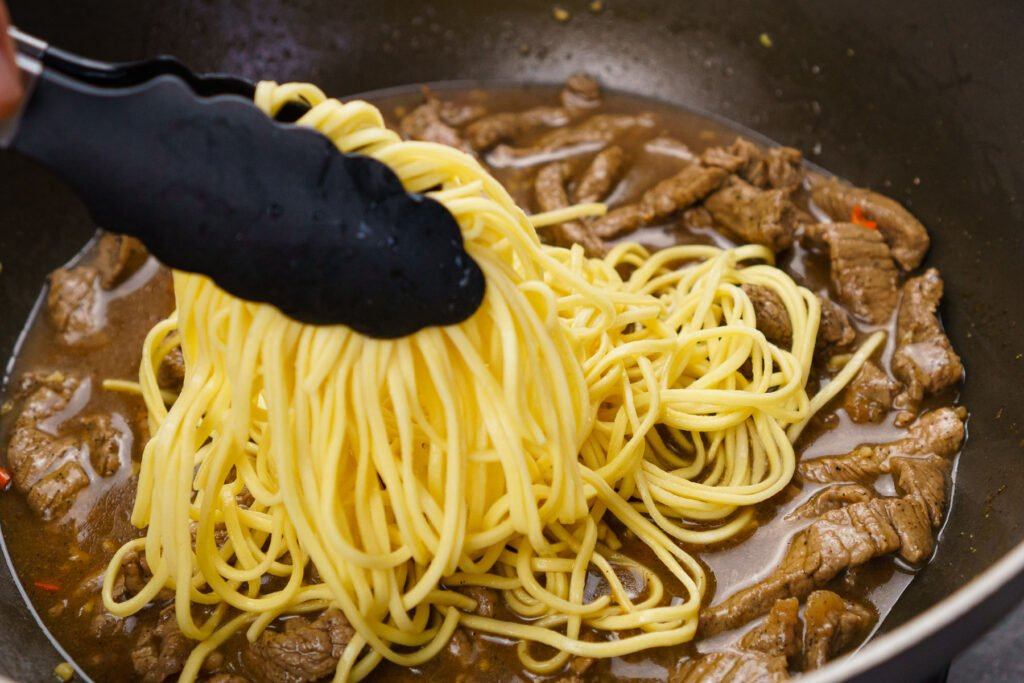 Placing in the egg noodles on top of the beef strips with black and silver tongs
