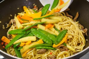 Pouring the Mangetout,baby corn and chopped orange pepper on top of the noodles and beef strips cooking in a wok