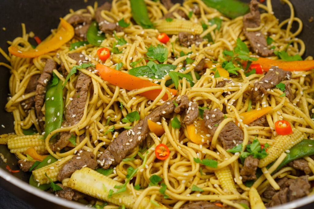 Beef stir-fry strips with noodles cooked in a spicy stir-fry sauce made in a wok