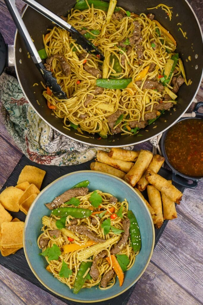 Beef Stir-fry with noodles in a wok served with spring rolls, sweet chilli sauce and crackers on the side and the stir fry served in a blue bowl