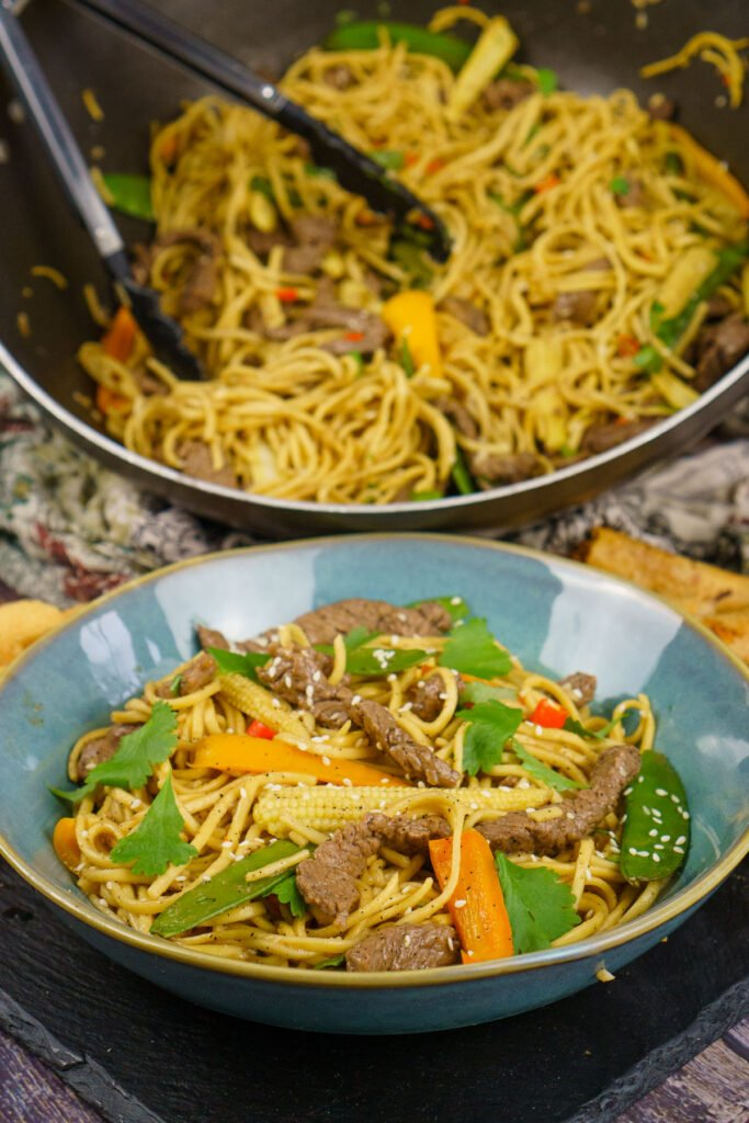 Beef Stir-fry with noodles served in a blue bowl with the beef stir fry served in a wok in the background