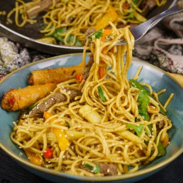 Beef Stir-fry with noodles in a blue bowl with spring rolls on the side and the noodles being picked up with a fork