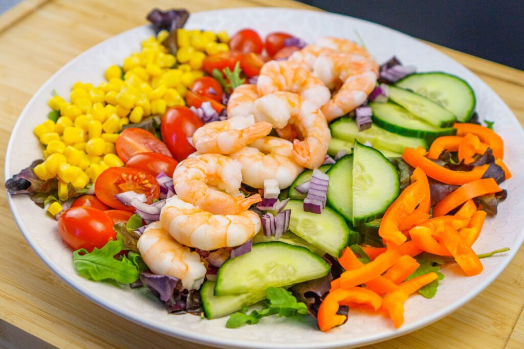 A plate of salad on a white plate consisting of rocket leaves,sweet corn, chopped cherry tomatoes, cucumber and orange pepper and King prawns in the middle on top of the leaves