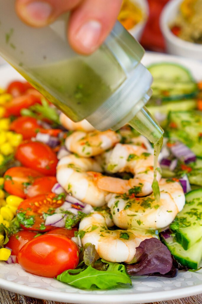 Drizzling chilli dressing over our king prawn salad from a plastic bottle by hand