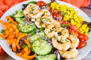 Summer King Prawn Salad served on a white plate consisting of rocket leaves,sweet corn, chopped cherry tomatoes, cucumber, orange pepper, chilli salad dressing and sprinkled desiccated coconut all over the top