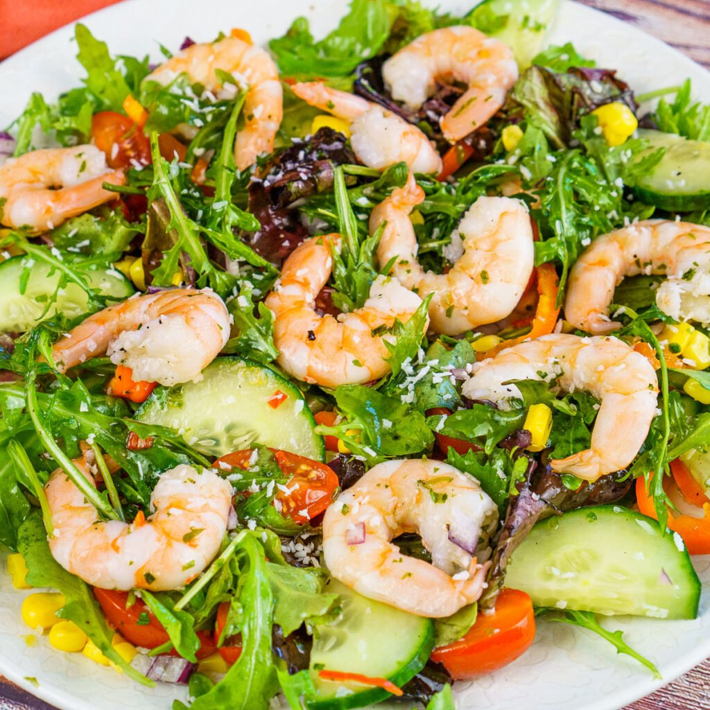 Prawn Salad recipe served on a white plate with chilli dressing and desiccated coconut sprinkled over the top