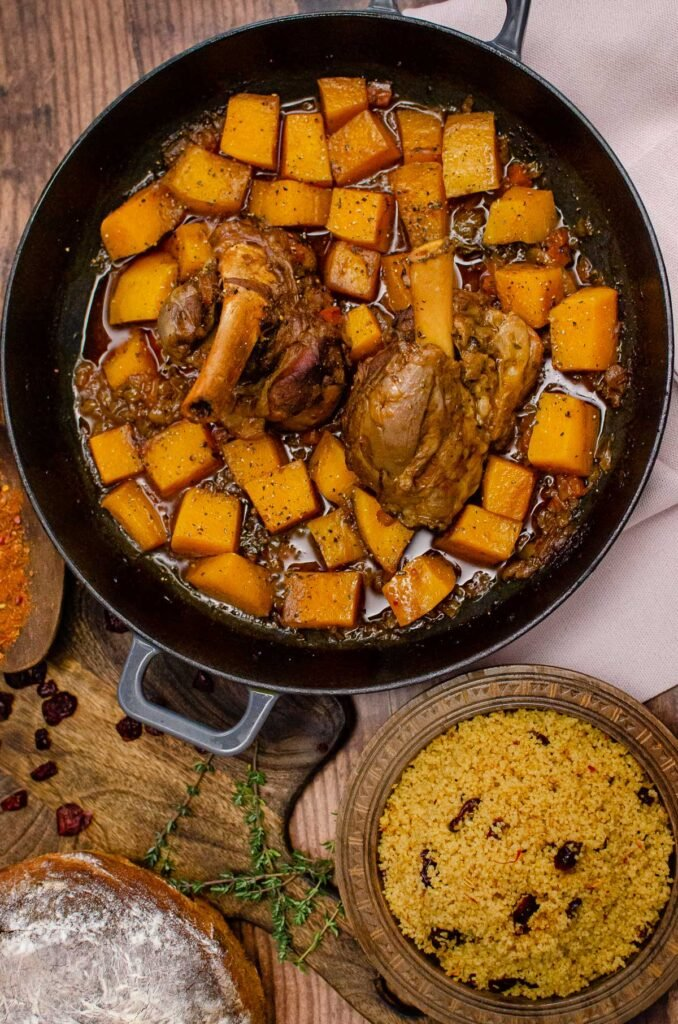 Two cooked Persian lamb shanks in a cast iron pan with chunks of butternut squash in a sauce with a wooden bowl of couscous and a cob loaf of bread on the side