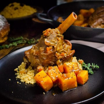 Persian Lamb Shank served on saffron couscous and chunks of butternut squash on the side on a black plate