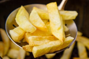Air fried chips on a silver slotted ladle.