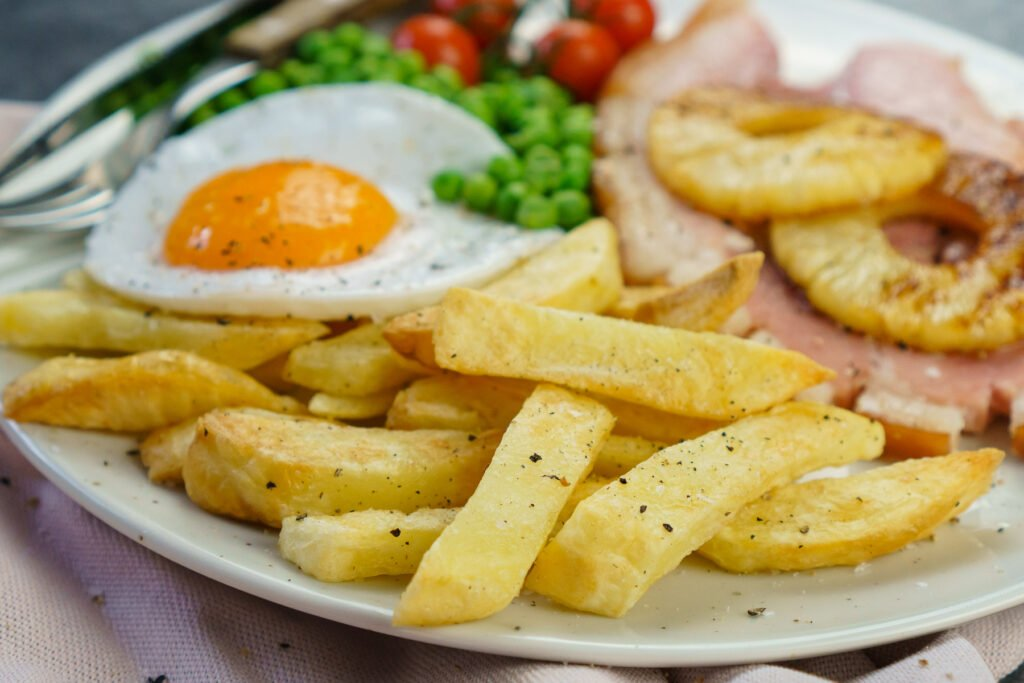 Homemade Air Fryer Chips served with gammon steak, pineapple rings, egg, peas and tomatoes