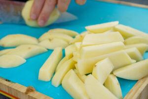 Fresh cut chips being cut on a blue board