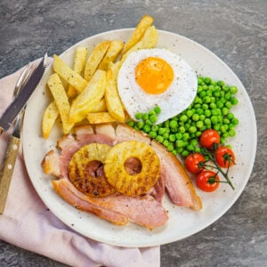 Gammon egg and homemade chips served with vined cherry tomatoes,peas and two pineapple rings on a white plate