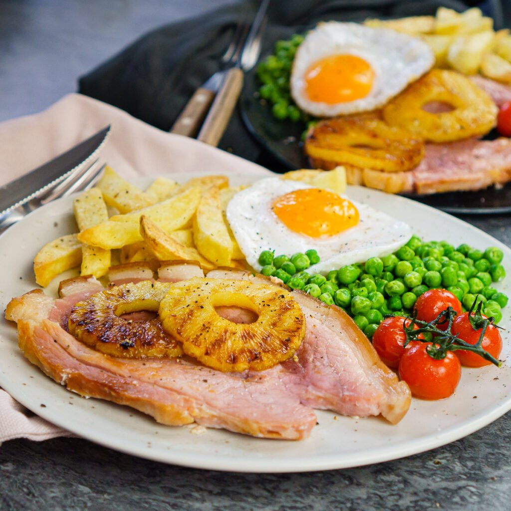 Gammon steak served with homemade chips, duck egg, peas, vined cherry tomatoes and two pineapple rings on a white plate
