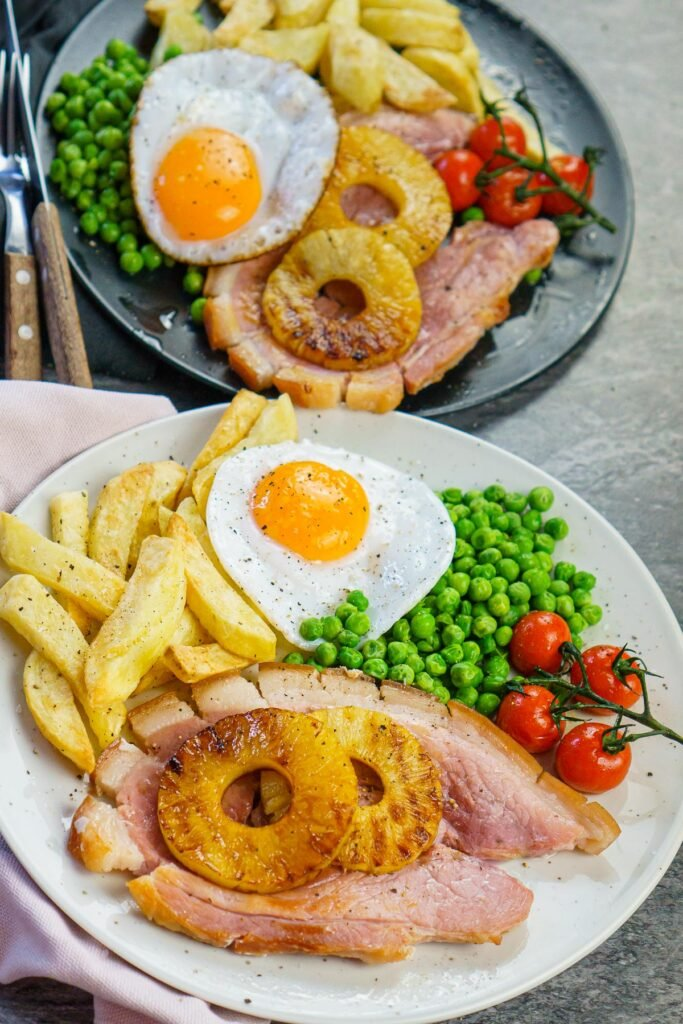 Two plates of ham egg and chips. Cooked gammon steaks served with chips, egg, peas, vine-ripened tomatoes and pineapple rings
