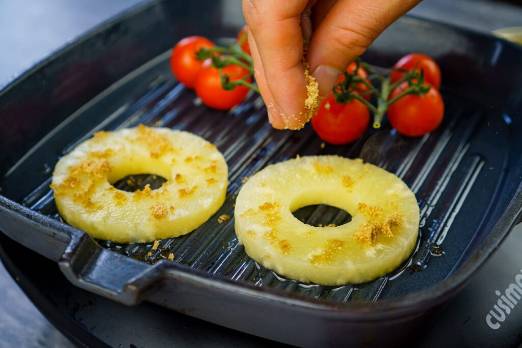 Two pineapple rings and vine cherry tomatoes cooking on a griddle pan and brown sugar being sprinkled over the top of the pineapple rings by hand