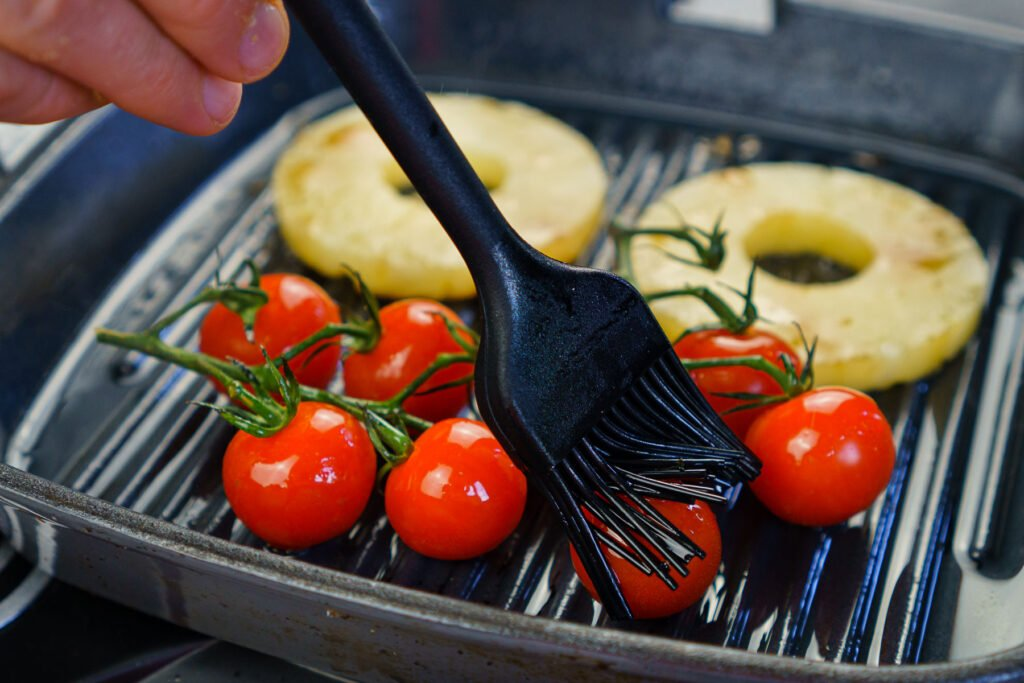 Brushing olive oil over vined cherry tomatoes with a black brush
