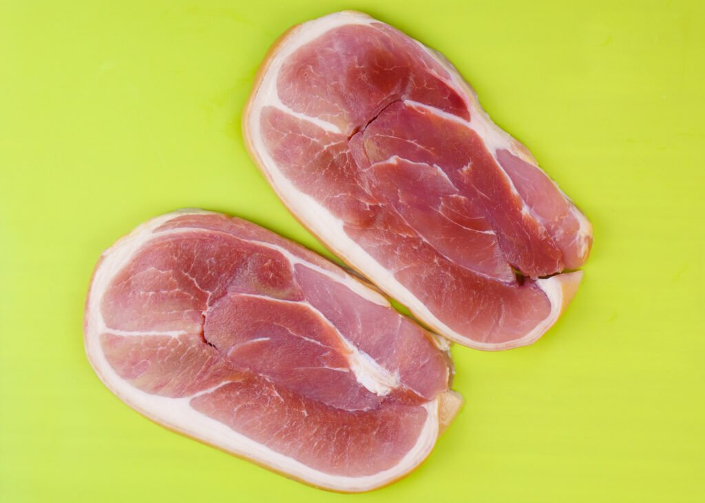 Two gammon Steaks on a green chopping board