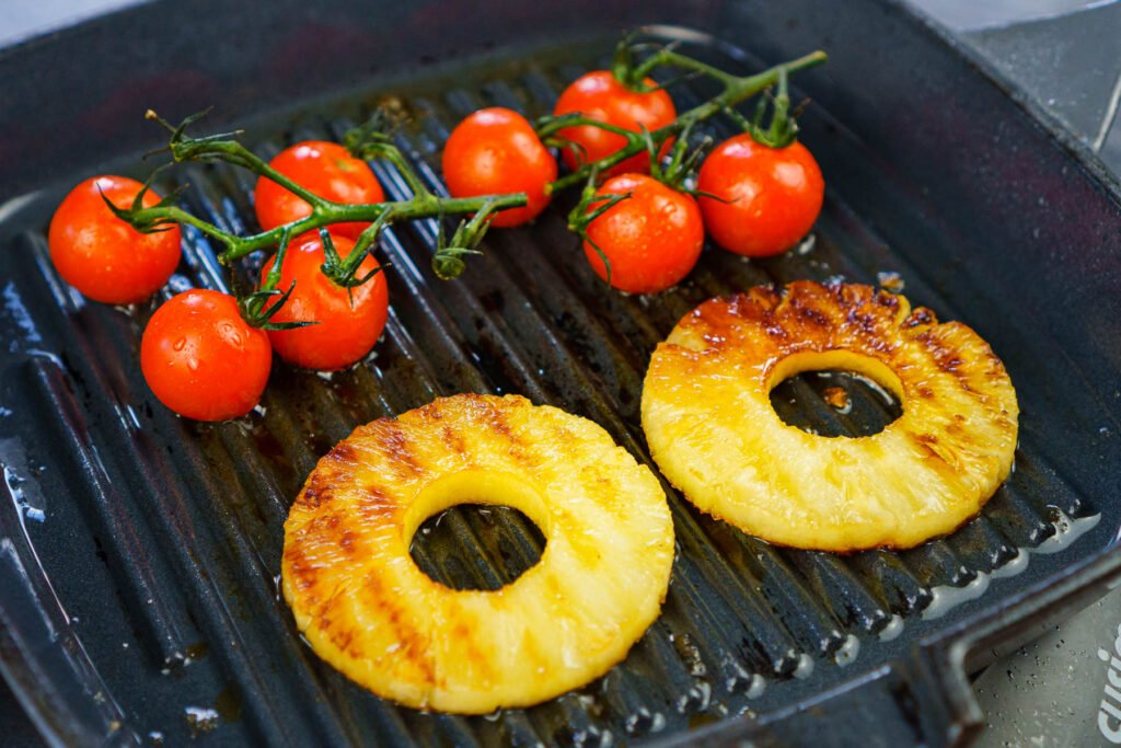 Two pineapple rings and vined cherry tomatoes cooking on a griddle pan