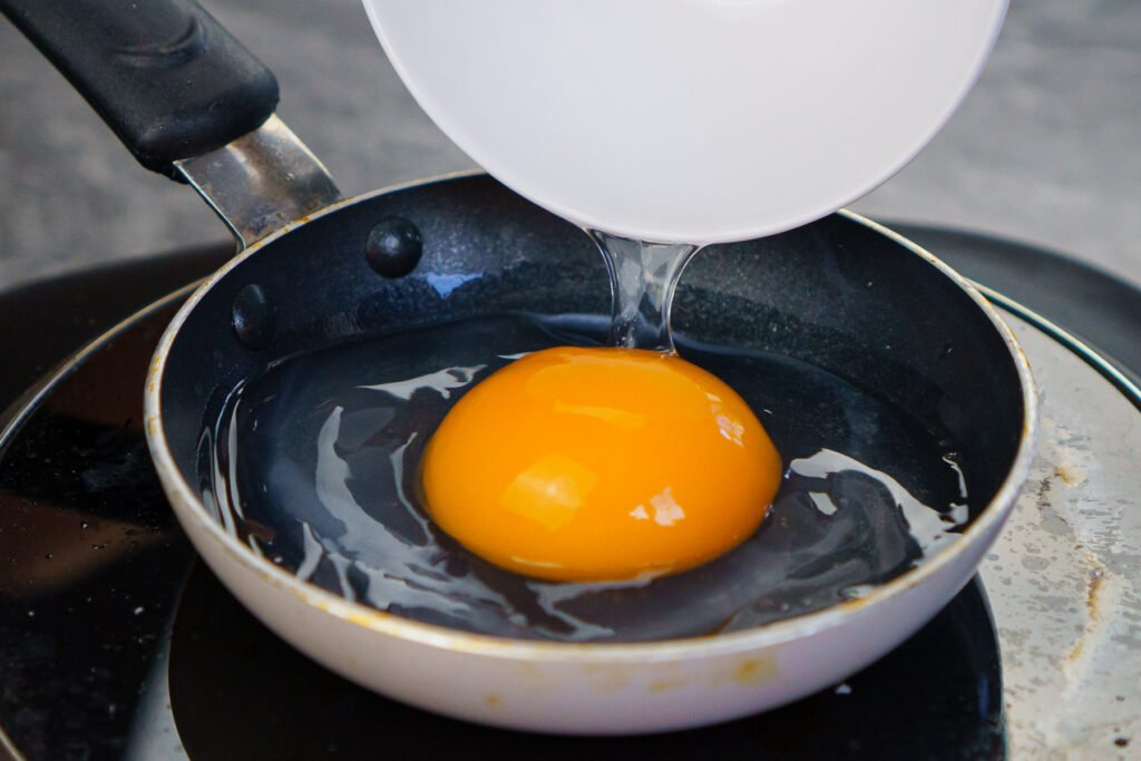 Pouring a duck egg in a mini frying pan